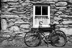 Vada in bicicletta fuori di vecchio cottage rurale in Irlanda Immagine Stock
