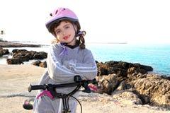 Vada in bicicletta il piccolo casco felice di colore rosa della ragazza in mare roccioso fotografia stock libera da diritti