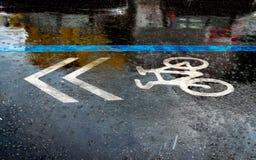 Vada in bicicletta il simbolo sulla strada nel tempo di pioggia Immagini Stock