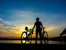 Vada in bicicletta il supporto del cavaliere sul fiume che guarda la luce solare e rilassi Fotografia Stock