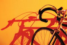 Vada in bicicletta l'estratto con la forte ombra dell'ed su giallo Immagine Stock Libera da Diritti