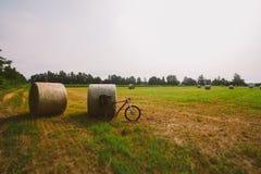 Vada in bicicletta nel campo con le grandi balle rotonde di paglia fotografia stock