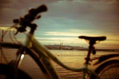 Vada in bicicletta nella sera, il sole sopra la bicicletta, con il tramonto e la r Immagine Stock