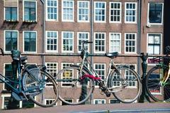 Vada in bicicletta sul ponte del canale di fiume della via della città a Amsterdam Immagini Stock Libere da Diritti