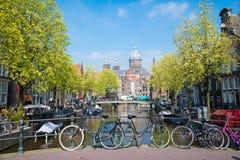 Vada in bicicletta sul ponte del canale di fiume della via della città a Amsterdam Immagini Stock