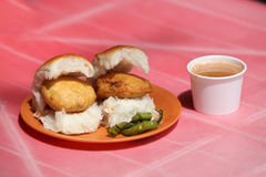 Vada Pav. An Indian snack called Vada Pav which is like a potato burger or tikki n a bread, with a cup of tea Royalty Free Stock Photo