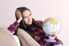 Vada su un'avventura Donna che sogna del viaggio intorno al mondo, guardante in camera con il globo a disposizione Castana svegli Fotografia Stock
