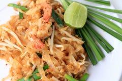 Vaddera thailändska stekte under omrörning risnudlar med räka i den vita plattan med glidbanacitronen och den gröna grönsaken Den royaltyfri foto