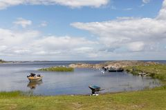 Swedish archipelago and a small harbor with boats and a man prep Stock Images