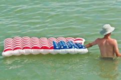Vadear masculino novo na água tropical e aferrar-se para arejar mattres imagens de stock royalty free
