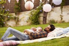 Vader With Baby Relaxing op Deken in Tuin samen royalty-vrije stock foto's