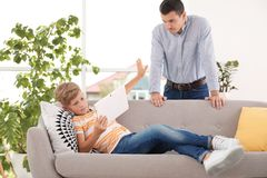 Vader berispend kind terwijl hij die tablet thuis gebruiken royalty-vrije stock foto's