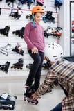 Vader bijwonende zoon in het proberen op rolschaatsen in sportenopslag stock afbeeldingen