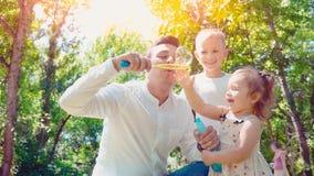 Vader blazende zeepbels voor zoon en weinig dochter in het park, het concept van de levensstijlfamilie stock video