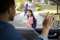 Vader In Car Dropping van Dochter in Front Of School Gates stock foto's
