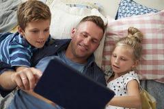 Vader And Children Lying op Vloer die Digitale Tablet gebruiken royalty-vrije stock foto's