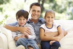 Vader And Children Sitting op Sofa At Home Royalty-vrije Stock Afbeeldingen