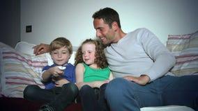Vader And Children Sitting op Sofa Watching-TV samen stock videobeelden