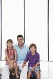Vader With Children Sitting samen thuis Stock Foto's
