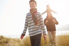 Vader And Children Walking door Duinen op de Winterstrand royalty-vrije stock fotografie