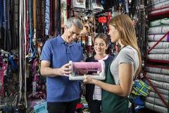 Vader And Daughter Buying Cat Scratcher From Saleswoman stock afbeeldingen
