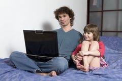 Vader die aan laptop van huis werkt Stock Afbeeldingen