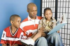 Vader die aan zijn kinderen leest stock foto's