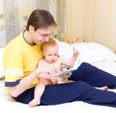 Vader die aan zijn zoon leest Royalty-vrije Stock Afbeeldingen