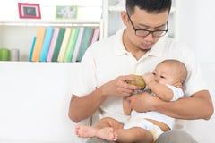 Vader die baby met de fles grootbrengen Stock Foto's
