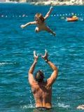 Vader die baby over het water werpen royalty-vrije stock foto