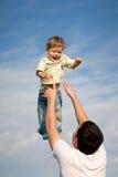 Vader die babyjongen werpen Stock Foto