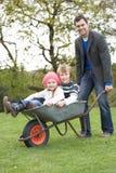 Vader die de Rit van Kinderen in Kruiwagen geeft Royalty-vrije Stock Foto's