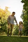 Vader die in de weide met dochter lopen Stock Afbeelding