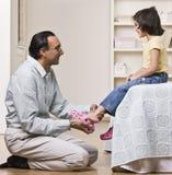 Vader die Dochter met Schoenen helpt Stock Foto
