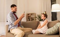 Vader die dochter thuis fotograferen door cellphone stock afbeelding