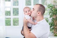 Vader die en zijn kleine zoon koesteren kussen stock fotografie