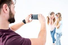 Vader die foto van moeder en dochter het luisteren muziek met hoofdtelefoons nemen stock foto