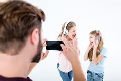 Vader die foto van moeder en dochter het luisteren muziek met hoofdtelefoons nemen en het zingen stock foto's