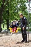 Vader die gehandicapte jongen in speciale behoeftenschommeling duwt Stock Afbeelding