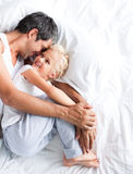 Vader die haar dochter op bed huggling stock foto