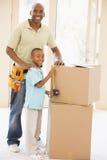 Vader die hulpmiddelriem door zoon in nieuw huis draagt Royalty-vrije Stock Afbeelding