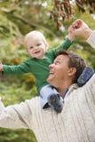 Vader die jonge zoonsrit op schouders geeft Royalty-vrije Stock Foto's