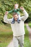 Vader die jonge zoonsrit op schouders geeft Stock Afbeelding