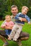 Vader die kinderen omhelst Royalty-vrije Stock Afbeeldingen