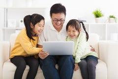 Vader die laptop met meisjes met behulp van Stock Fotografie