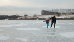 Vader die met dochterijs op bevroren meer schaatsen stock videobeelden