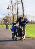 Vader die met gehandicapte zoon in rolstoel lopen Royalty-vrije Stock Fotografie
