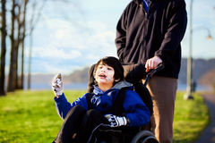 Vader die met gehandicapte zoon in rolstoel lopen Stock Afbeeldingen
