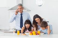 Vader die met mobiele telefoon met zijn familie roepen die breakfas eten Stock Foto