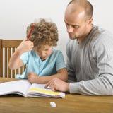 Vader die met thuiswerk helpen Stock Afbeelding